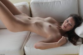 Tiffany Thompson is totally nude laying on her back with her pelvis arched up.