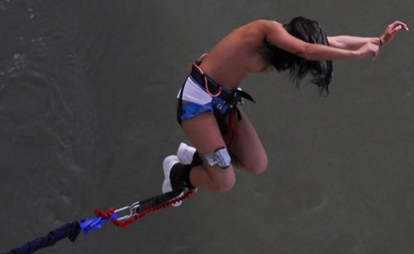 A topless brunette is hanging from bungee cord over water.