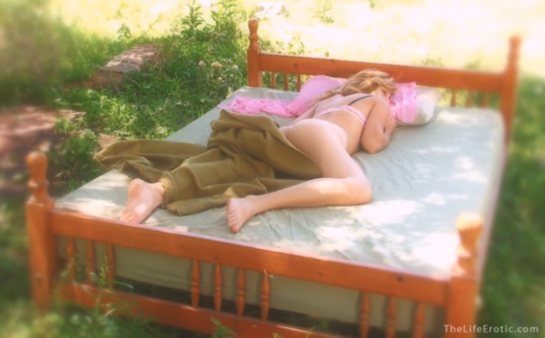 Blonde Angie is lying on her belly on a bed in a forest.