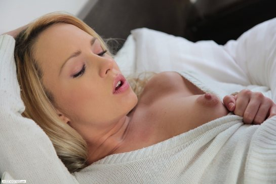 A blonde is lying down closing her eyes as she exposes a puffy nipple.