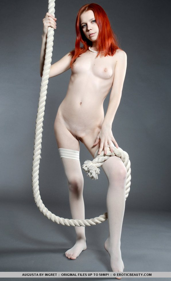 Redhead Augusta is naked and holding a big rope.