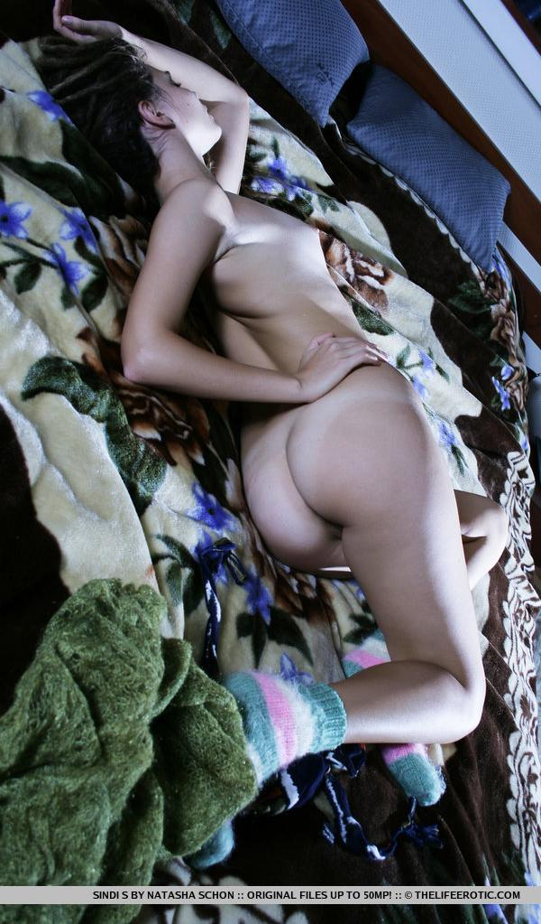 Sindi is lying sideways naked in bed showing her beautiful ass.
