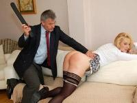 Blonde Amelia is bent over the sofa as she gets spanked by a man in a suit.