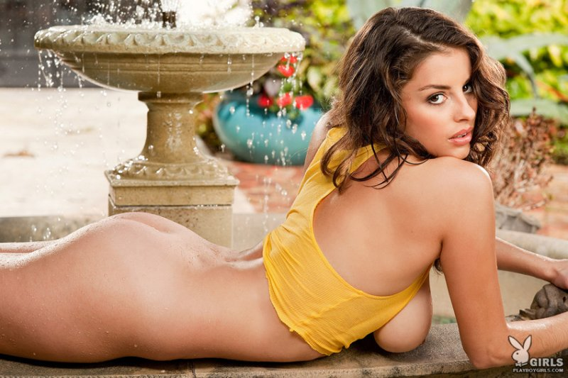 Beautiful brunette lying nude next to water fountain