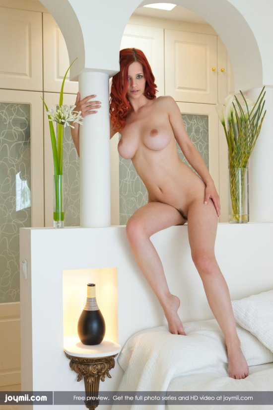 A beautiful nude young woman with full breasts and bright red hair leans against a white pillar.