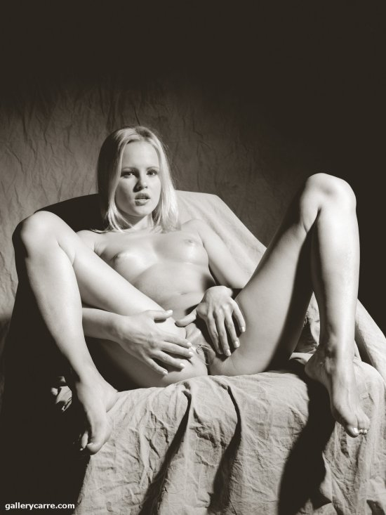 Nude blonde with legs spread exposing breasts and vagina