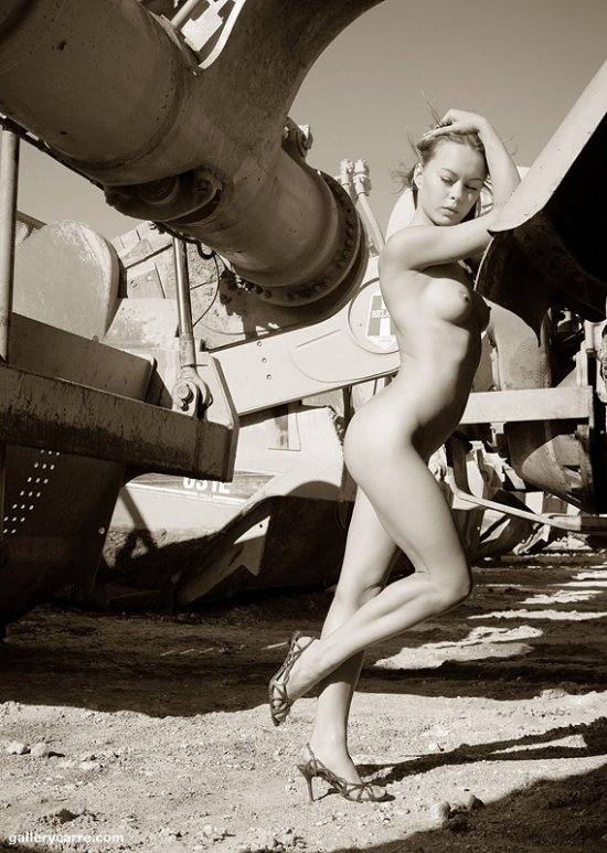 Totally nude blond standing next to a heavy industrial machine.
