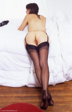 Nude woman laying on belly exposed vagina wearing garters and stockings
