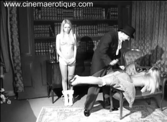 Nude blonde getting a spanking from a man wearing an old fashioned suit as another girl stands next to her.