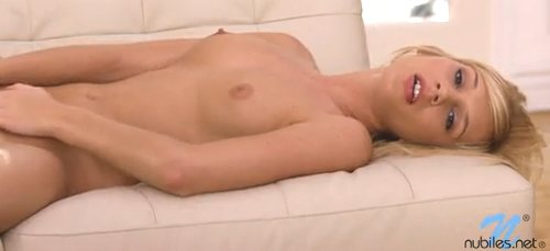 Hayden Hawkins is a pretty blonde nude with full breasts laying on a couch.