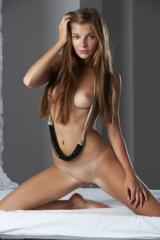 Nude beauty Belle is kneeling on a bed with her legs spread exposing her full breasts and shaved pussy.
