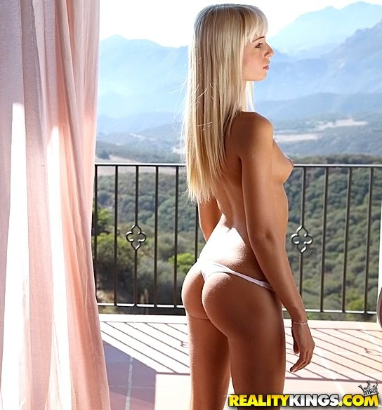 Erica is a topless platinum blonde in a g-string standing on a balcony overlooking a mountain range.