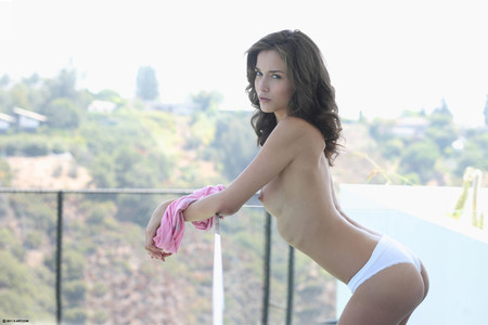 Malena's breasts are bare and she is wearing white panties as she leans on a balcony railing.