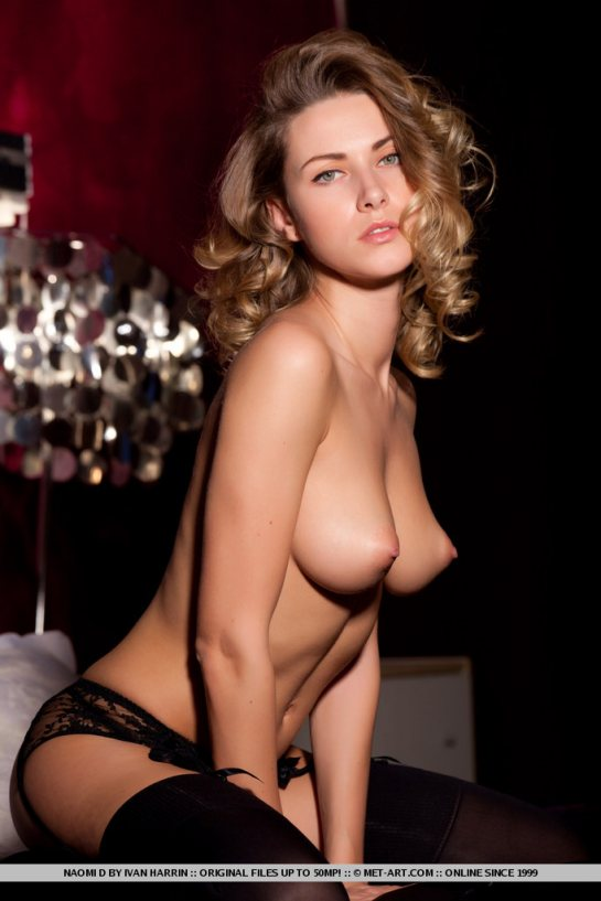 Topless beauty Naomi wears panties, garters and stockings and shows her full pointed breasts.