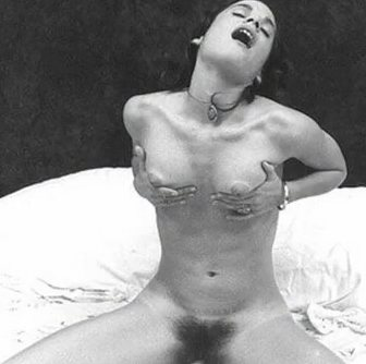 In this old time black and whit photo a nude brunette with pubic hair is sitting on a bed with her legs spread.