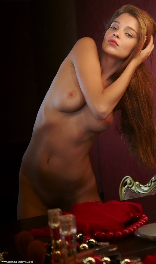 A beautiful nude is stroking her long red hair.
