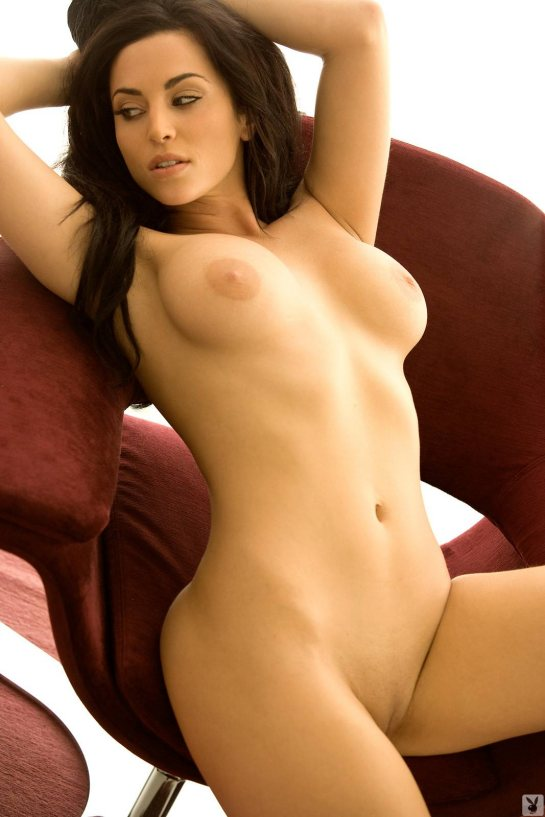 A big breasted brunette stretches her arms in a full frontal nude pose.