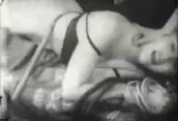 In this still from a 1940's movie a young woman is tied up and getting her butt paddled.