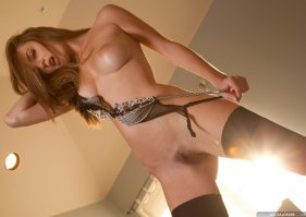 Dakota Rae stands fully nude with her legs spread revealing her bushy pubic hairs and her full and firm breasts.