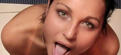 A pretty brunette has her mouth opened wide enough to show her tongue.