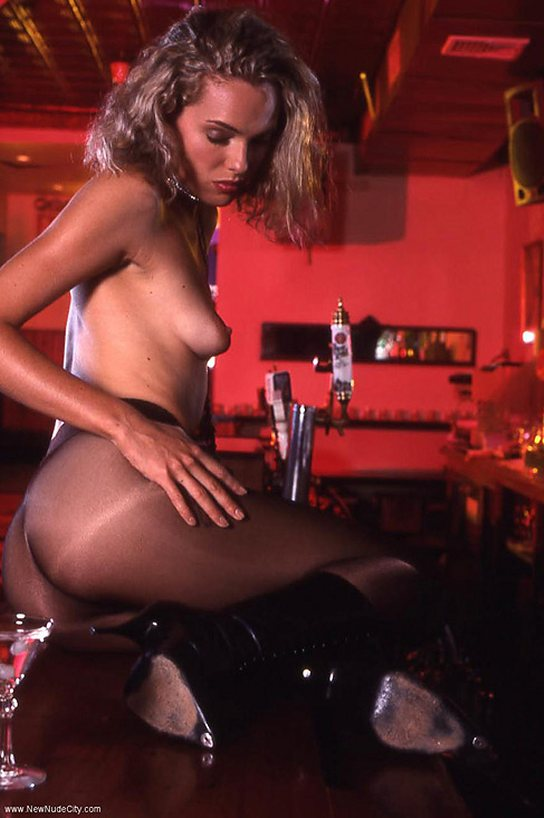 A topless young woman is sitting on a tavern bar top wearing see-through  pantyhose.