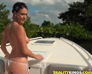 A topless brunette stands at the bow of a boat.