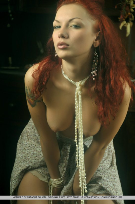 Topless Erotic Beauty,  Monika has long hair dyed metallic red and is wearing pearls.