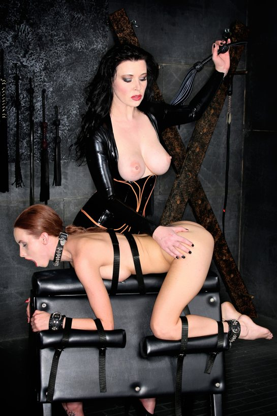 A totally nude red head is strapped down on her knees and elbows as a lesbian lifts a whip over her ass.