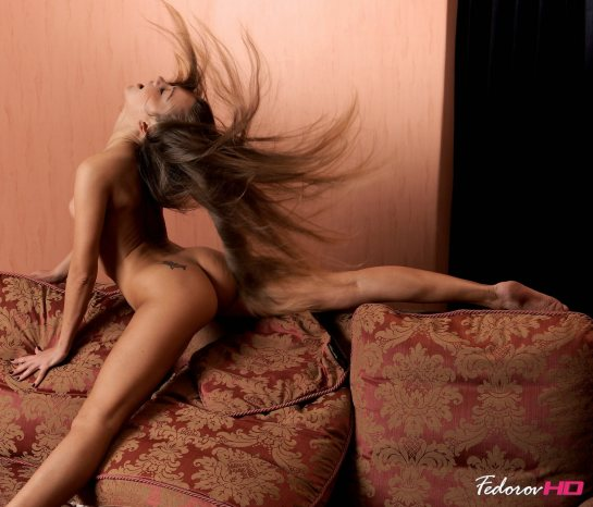 A beautiful young woman with extremely long hair tosses her head so that her hair is strewn in all directions.