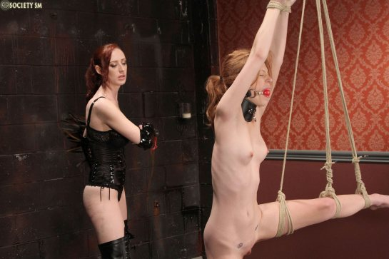 A naked redhead is standing tied-up and whipped by a woman wearing black latex.