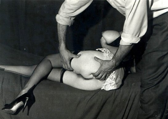 In this black and white photo from the 1930's a man with his shirt sleeves rolled up is squeezing a woman's naked butt as she lays sideways wearing only mesh stockings.