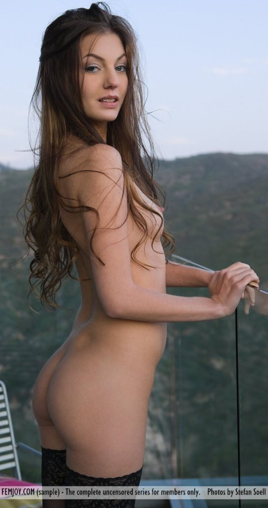 Beautiful long haired nude brunette, Alexis, is standing on a balcony over looking a mountain range,