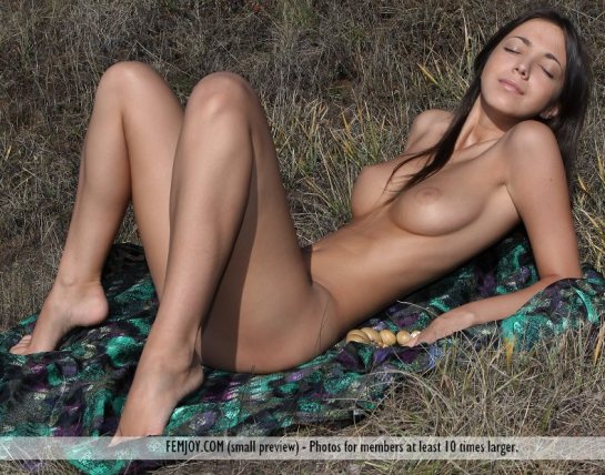 A fully nude thin brunette with very large full breasts is resting on her elbows with her eyes closed.