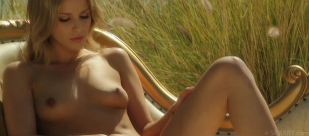 Nude blonde, Jasmine sits on a wicker chair masturbating in seaside tall grass.