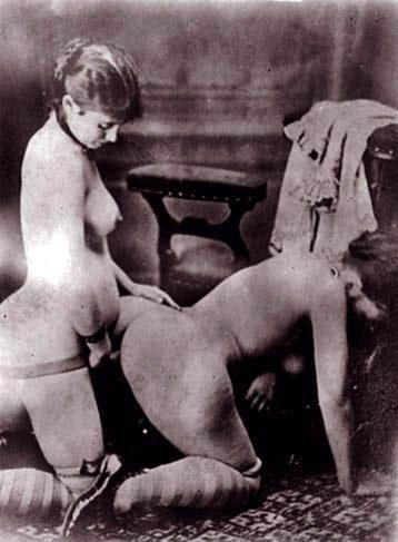 In this very old black and white photo a nude woman is getting fucked doggy style by a woman wearing  a strap-on dildo.