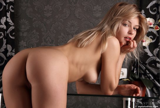 Fully nude blonde Andrea is bent over with her elbows resting on a reflective glass table.