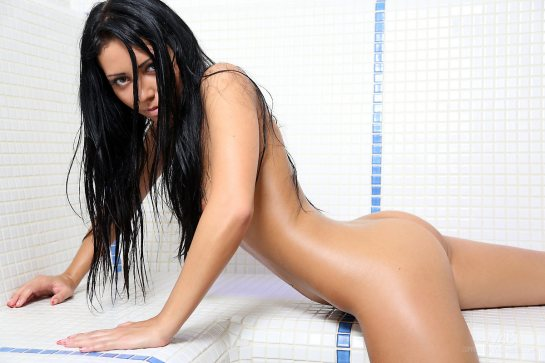 A thin nude brunette with long raven black hair is resting on her hands.