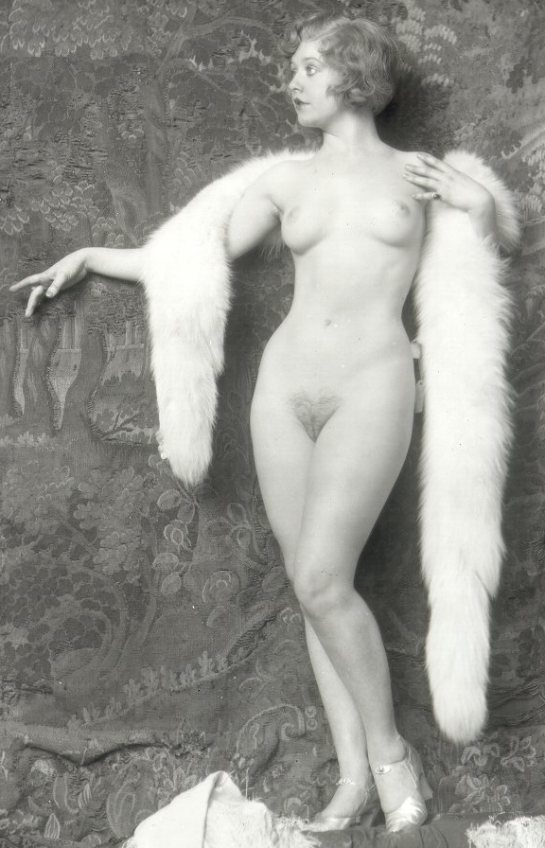 In this old-time black and white photo a blonde woman with big breasts and pubic hair is standing naked..