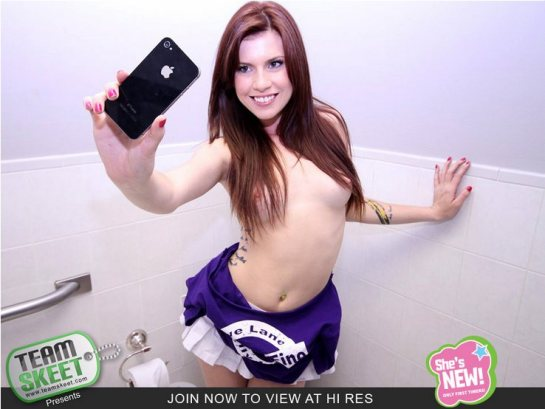 Annie Whorehall is topless and smiling as she takes her own picture.
