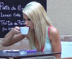 A pretty long haired blonde is drinking coffee in a coffee shop.