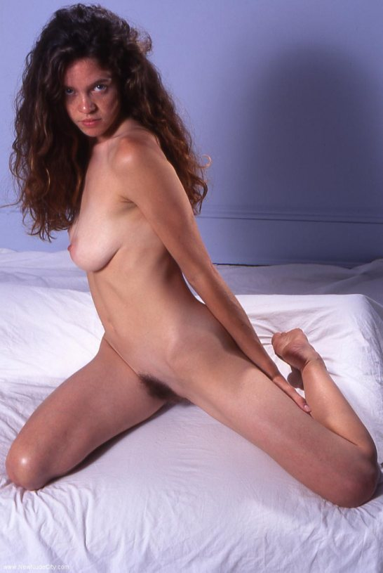 A girl with long dark red hair and bushy pubic hair is in bed naked with her legs stretched.