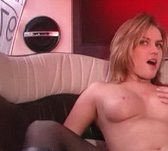 A topless blonde is in the backseat of a limo with her mouth open and her knee up as an unseen man finger fucks her.