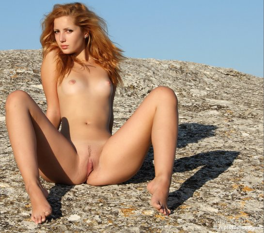 Fully nude redhead Elisa is sitting on rocky ground with her legs spread showing her vulva.