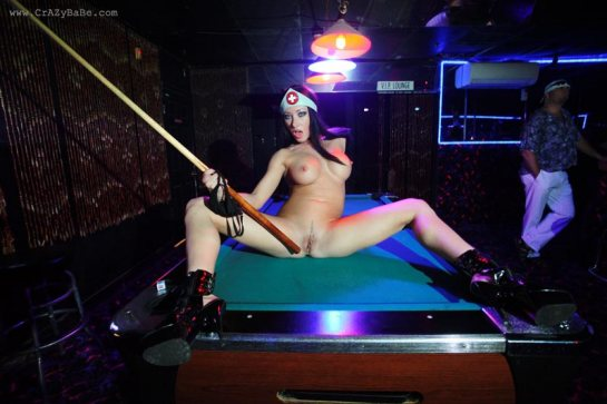 Nadia Nitro is on a pool table naked with her legs spread and pointing to her pussy with a pool cue.