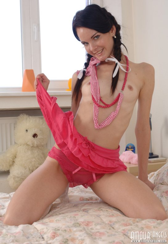 Simona is a small breasted topless brunette kneeling in bed and lifting her nightie to show her see-through panties.