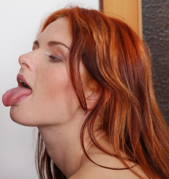 Redhead Amber has her eyes closed and her tongue out.