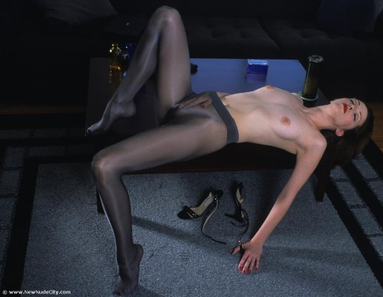 A topless lady spreads her legs and has her hand down her see-through pantyhose.