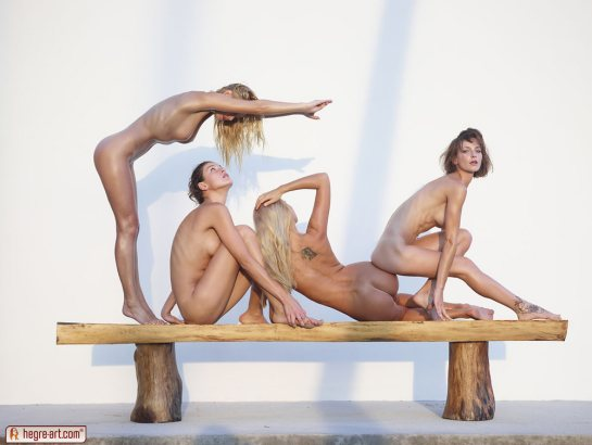 Four naked girls are posing on a bench.