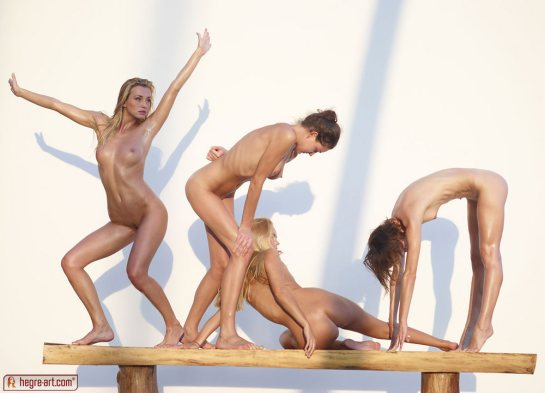 Four naked young women are stretching.