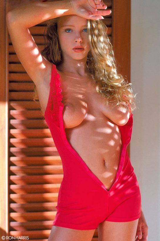 Gorgeous blonde Kelly Lord's lingerie is open showing her beautifully formed breasts.
